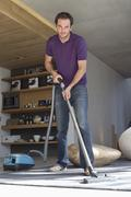 Man cleaning house with a vacuum cleaner Stock Photos