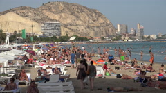 Crowded Alicante beach with mountain backdrop Stock Footage