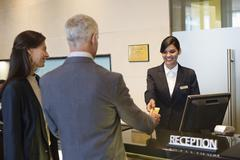 Business couple paying with a credit card at the hotel reception counter - stock photo
