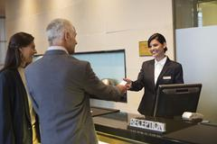 Business couple getting key card at the hotel reception counter - stock photo