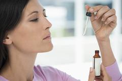 Close-up of a woman taking homeopathic medicine Stock Photos
