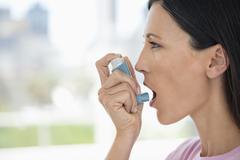 Close-up of a woman using an asthma inhaler Stock Photos