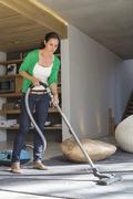 Woman cleaning house with a vacuum cleaner Stock Photos