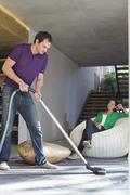 Man cleaning house with a vacuum cleaner with his wife sitting on a seat Stock Photos