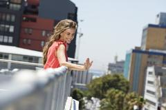 Smiling woman leaning against a railing and waving her hand Stock Photos