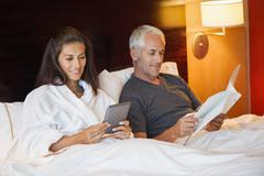 Woman using a digital tablet with her husband reading a book in a hotel room Kuvituskuvat