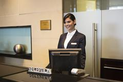 Receptionist standing at the hotel reception counter and smiling - stock photo