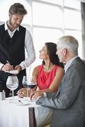 Waiter taking orders from a couple in a restaurant - stock photo