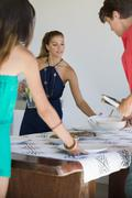 Friends arranging plates on a dining table - stock photo