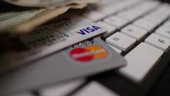 ECOMMERCE Dolly over Credit cards and $10 bill on keyboard Stock Footage