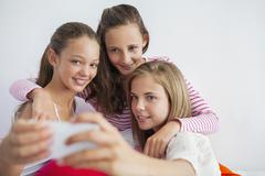Three girls taking a picture of themselves with a mobile phone at a slumber Stock Photos
