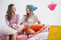 Girls sitting on the bed and talking to each other at a slumber party Stock Photos