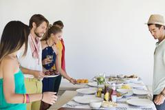Friends arranging food on a dining table Stock Photos
