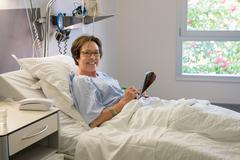 Woman smiling on hospital bed - stock photo