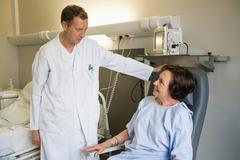 Male doctor assisting female patient in hospital - stock photo