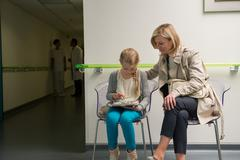 Woman with her daughter sitting in hospital waiting room Kuvituskuvat