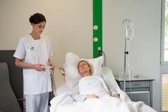 Medical attendant examining a female patient in hospital bed Stock Photos
