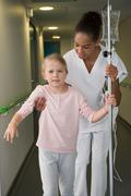 Female nurse helping to a girl patient to walk in hospital corridor Kuvituskuvat