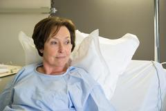 Woman sitting in hospital bed - stock photo