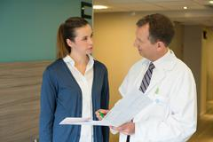 Male doctor discussing medical report with a woman in hospital - stock photo