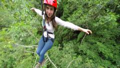 Young women on zip line over the dense rainforest, 3rd person camera Stock Footage