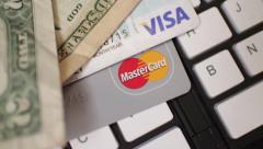 ECOMMERCE Overhead Rotate Over Credit cards and cash on keyboard Stock Footage