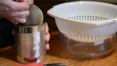 Open tin can and filling peach in a bowl Stock Footage