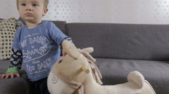 Baby boy and his horse toy Stock Footage
