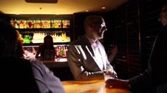 Chic lounge - after work men in suits enjoying drinks - dolly shot Stock Footage