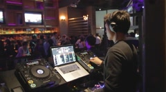 Dolly shot - Asian DJ mixing at trendy lounge Stock Footage