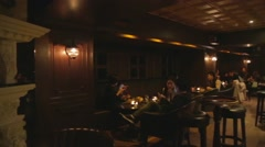 Asian people enjoying trendy speakeasy lounge - pan Stock Footage