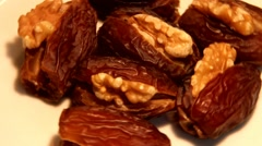Dates stuffed with walnuts  rotating  in front of camera on paper background Stock Footage