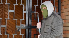 Robber with crowbar near gates - stock footage