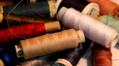 Coils and bobbins with colored thread, scattered on a white table Stock Footage