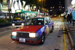 a taxi travels on the road in hong kong - stock photo