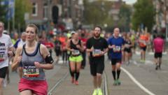Marathon runners running into focus on long lens Stock Footage