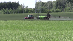 Red agricultural tractor spray oat field herbicides, pesticides Stock Footage