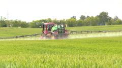 Farm tractor spray summer season green wheat crop field Stock Footage