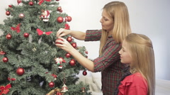 Happy woman decorating the christmas tree with her daughter Stock Footage