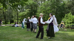 People dancing folk dances in pairs in park folk event Stock Footage