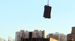 Construction site. Worker waiting for filing formwork with a crane. Stock Footage