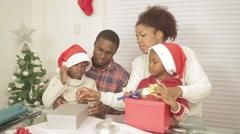 Black family preparing the christmas presentes - stock footage