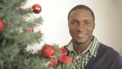 Black man decorating the Christmas tree Stock Footage