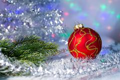 Red Christmas ball and tree branch on the background lights garl Stock Photos