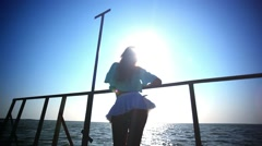 Carefree sexy woman in sunset standing on the pier. View up at ass. HD. Stock Footage