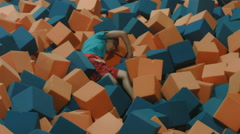 KID TRYING TO CLIMB OUT OF A FOAM PIT. Stock Footage
