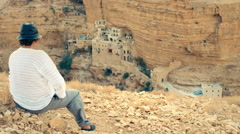 A man looking at the St. George Monastery, Israel, desert Stock Footage