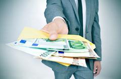 man giving an envelope full of euro bills - stock photo
