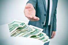 man taking an envelope full of dollar bills - stock photo