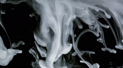 White ink and particles floating like smoke, close up, slow motion Stock Footage